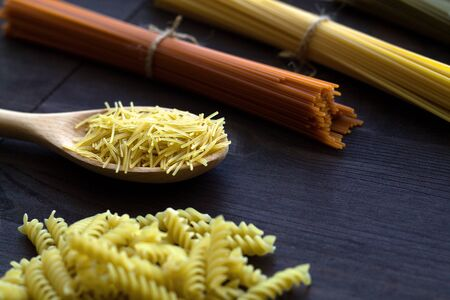 raw pasta on a wooden table. uncooked wheat and tomato spaghetti, fusilli, penne on a dark background with copy space. Italian Cuisine
