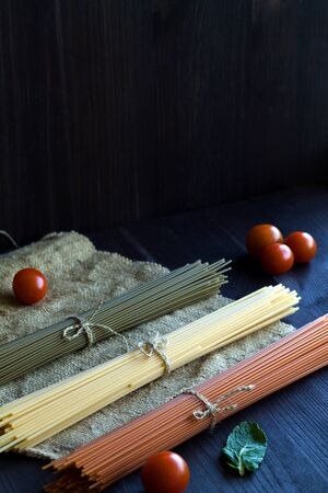 raw spaghetti, red cherry tomatoes and green leaves with sackcloth on a wooden table with copy space. top view. uncooked Spinach spashetti and wheat spaghetti on a black background. Italian Cuisine. vertical Banque d'images - 150179270