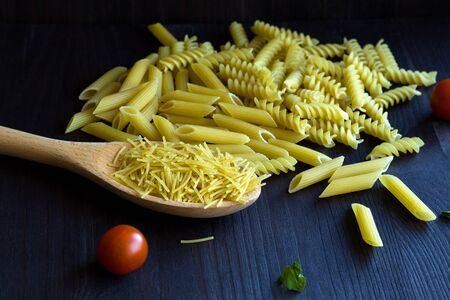 raw macaroni with fusilli, penne with cherry tomatoes on a black background. different types of Italian pasta with a wooden spoon on a table with copy space.
