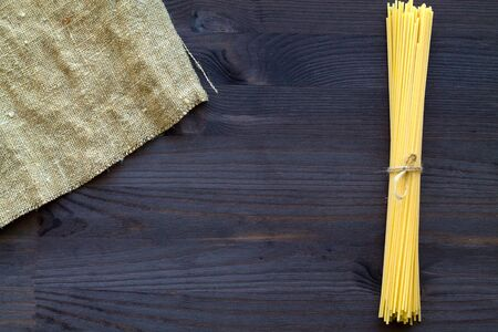 wheat spaghetti on wooden table. raw pasta with sackcloth on black background with copy space. top view. Italian Cuisine.