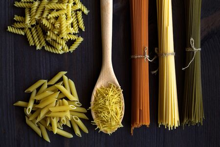 spaghetti and pasta on a wooden table. top view. uncooked wheat, Tomato and Spinach spaghetti and fusilli, penne on a dark background. Italian Cuisine Banque d'images