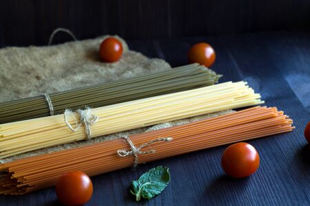 raw spaghetti, red cherry tomatoes and green leaves with sackcloth on a wooden table with copy space. top view. uncooked Spinach spashetti and wheat spaghetti on a black background. Italian Cuisine