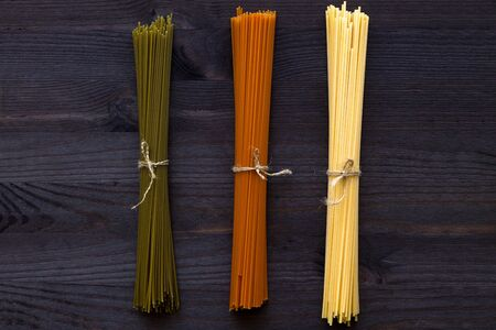 raw spaghetti on a wooden table with copy space. top view. uncooked wheat, Tomato and Spinach spaghetti on a dark background. Italian Cuisine Banque d'images