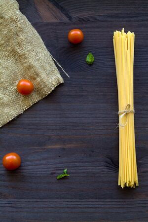 Italian Cuisine. raw spaghetti, red cherry tomatoes and green leaves with sackcloth on a wooden table with copy space. top view. uncooked wheat pasta on a black background. vertical