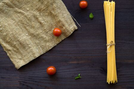 raw spaghetti, red cherry tomatoes and green leaves with sackcloth on a wooden table with copy space. top view. uncooked wheat spaghetti on a black background. Italian Cuisine. Banque d'images