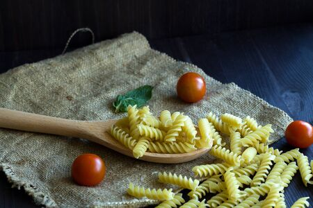 italian pasta with tomatoes. Fusilli pasta with sackcloth on wooden background. raw pasta on black background with copy space. Italian Cuisine. Banque d'images