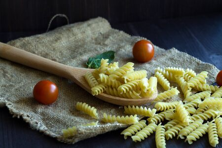 Italian Cuisine. italian pasta with tomatoes. Fusilli pasta with sackcloth on wooden background. raw pasta on black background with copy space.