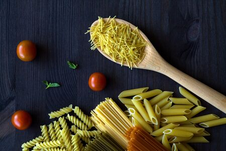 different types of Italian pasta on a wooden table with copy space. raw Spinach spashetti, wheat pasta and tomato spaghetti with fusilli, penne with cherry tomatoes on a black. top view.