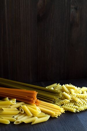 Italian Cuisine. different types of pasta on a wooden table with copy space. uncooked Spinach spashetti, wheat pasta and tomato spaghetti with fusilli, penne on a black background. vertical