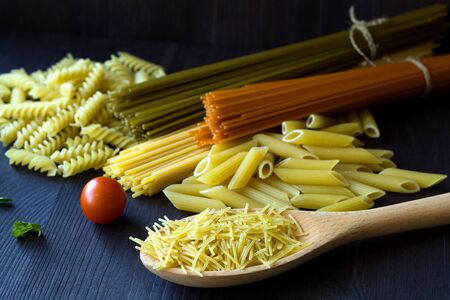 different types of Italian pasta with a wooden spoon on a table with copy space. raw Spinach spashetti, wheat pasta and tomato spaghetti with fusilli, penne with cherry tomatoes on a black background