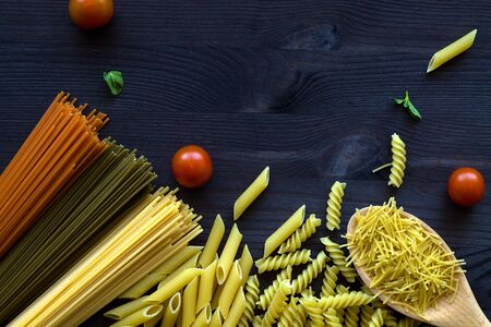 different types of Italian pasta with a wooden spoon on a table with copy space. raw Spinach spashetti, wheat pasta and tomato spaghetti with fusilli, penne with cherry tomatoes on a black. top view. Banque d'images