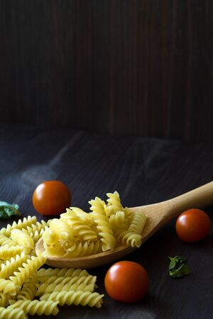 pasta and ingredients. Fusilli pasta with cherry tomatoes on wooden table. raw pasta on black background with copy space. Italian Cuisine. vertical