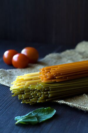 Italian Cuisine. raw spaghetti, red cherry tomatoes and green leaves with sackcloth on a wooden table with copy space. top view. uncooked tomato pasta, Spinach spashetti and wheat spaghetti on a black background. vertical