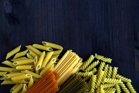 Italian Cuisine. different types of pasta on a wooden table with copy space. uncooked Spinach spashetti, wheat pasta and tomato spaghetti with fusilli, penne on a black background. top view.