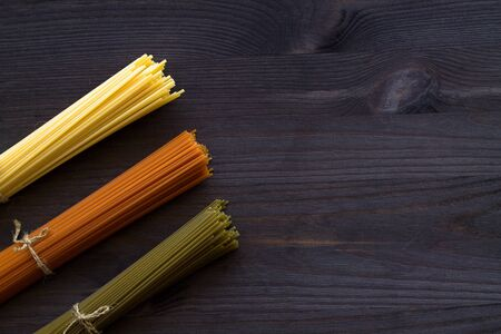 pasta on black. raw spaghetti on a wooden table with copy space. top view. uncooked wheat, Tomato and Spinach spaghetti on a dark background. Italian Cuisine Banque d'images