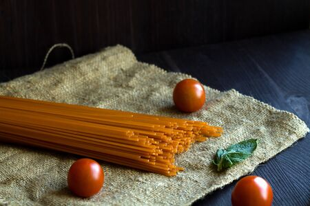 Italian Cuisine. raw spaghetti, red cherry tomatoes and green leaves with sackcloth on a wooden table with copy space. top view. uncooked tomato pasta on a black background.