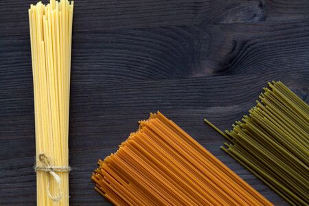 pasta on a black background. raw spaghetti on a wooden table with copy space. top view. uncooked wheat, Tomato and Spinach spaghetti on a black background. Italian Cuisine