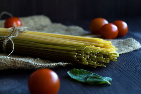 Italian Cuisine. raw spaghetti, red cherry tomatoes and green leaves with sackcloth on a wooden table with copy space. top view. uncooked Spinach spashetti and wheat spaghetti on a black background.