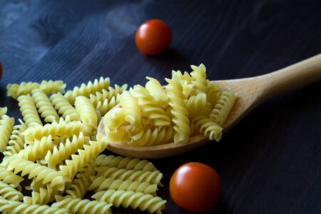italian pasta on wooden table. Fusilli pasta with red cherry tomatoes on wooden table. uncooked pasta on black background with copy space. Italian Cuisine.