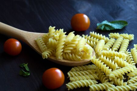italian pasta and ingredients. Fusilli pasta with cherry tomatoes on wooden table. raw pasta on black background with copy space. Italian Cuisine.