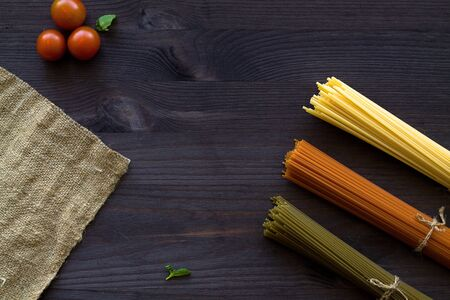 red cherry tomatoes and green leaves with sackcloth on a wooden table with copy space. top view. uncooked wheat, Tomato and Spinach spaghetti on a dark background. Italian Cuisine