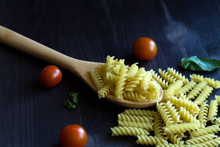 Fusilli pasta with cherry tomatoes on wooden table. raw pasta on black background with copy space. Italian Cuisine.