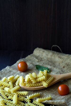italian pasta with tomatoes. Fusilli pasta with sackcloth on wooden background. raw pasta on black background with copy space. Italian Cuisine. vertical