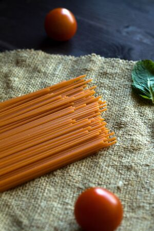 raw pasta with red cherry tomatoes on a black background. Uncooked tomato spaghetti with sackcloth on a wooden table. Italian Cuisine. top view Banque d'images