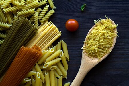 different types of Italian pasta on a wooden table with wooden spoon. raw Spinach spashetti, wheat pasta and tomato spaghetti with fusilli, penne with cherry tomatoes on a black background. top view.