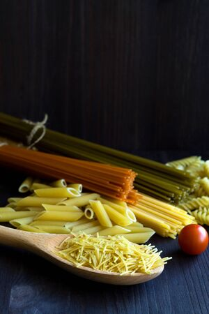 different types of Italian pasta with a wooden spoon on a table with copy space. raw Spinach spashetti, wheat pasta and tomato spaghetti with fusilli, penne with cherry tomatoes on a black. vertical