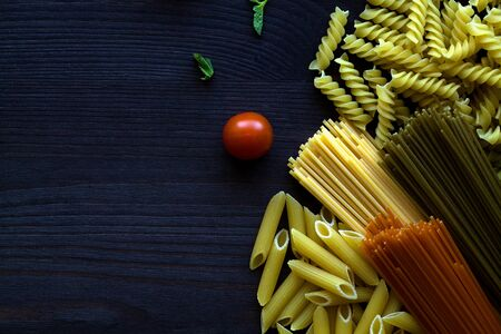 different types of Italian pasta on a wooden table with copy space. raw Spinach spashetti, wheat pasta and tomato spaghetti with fusilli, penne with cherry tomatoes on a black background. top view. Banque d'images