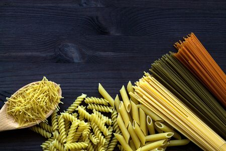Different types of raw pasta on a wooden table. uncooked wheat and tomato spaghetti, fusilli, penne on a dark background with copy space. top view. Italian Cuisine
