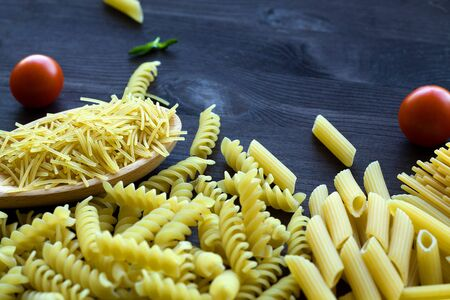 different types of Italian pasta with a wooden spoon on a table with copy space. raw macaroni with fusilli, penne with cherry tomatoes on a black background. top view.