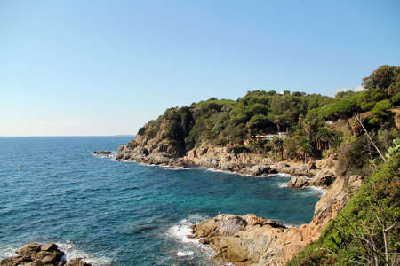 spain coast of the sea. Beautiful view of rocks with green pine trees and blue sea with waves under sky. Mediterranean Sea. Banque d'images