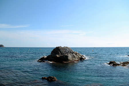 rocks in the sea. The sea. beautiful rocky coast of the sea with waves, horizon and blue sky with clouds. Mediterranean Sea