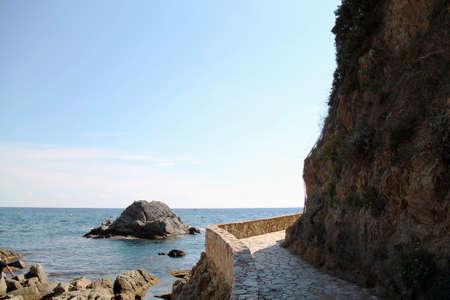 view of the coast of the mediterranean sea. rocky coast of the sea. Beautiful view of rocks with blue sea with waves, horizon under sunshine sky. Mediterranean Sea.