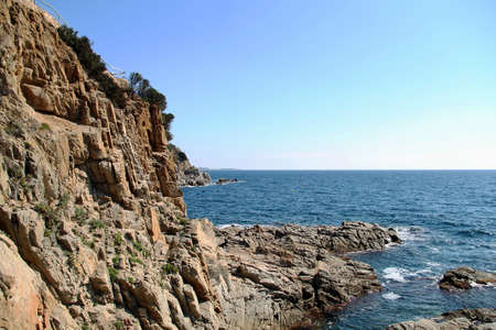 rocky coast of the sea. spain coast of the sea. Beautiful view of rocks with green pine trees and blue sea with waves under sunshine sky. Mediterranean Sea.