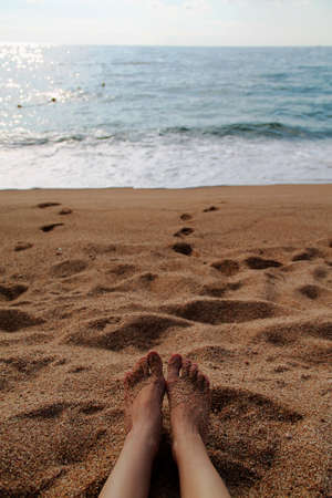 feet on the beach with yellow sand and blue sea. summer and rest day. vertical