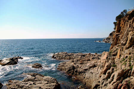 rocky coast of the mediterranean sea. Beautiful view of rocks with blue sea with waves, horizon under sunshine sky. Mediterranean Sea. Banque d'images