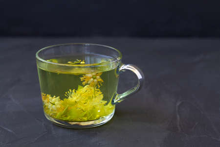 linden flowers tea.Cup of hot herbal tea with linden fresh flowers on a black table.Healthy lifestyle.glass cup of tea with green leaves on a black background.hot drinks.copy space