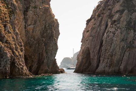 Passaggio tra le rocce nel mare. Scogliera rocciosa (Faraglioni della Madonna) del Mar Mediterraneo dell'isola di Ponza in Italia.
