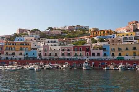 Port of the island of Ponza in the summer. The typical colored houses of the island of Ponza. Landscape of the harbor of Ponza. 版權商用圖片