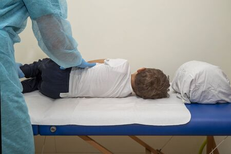 Physiotherapist performs evaluation on a child lying on the orthopedic bed, in a lateral position. Places the hands covered in disposable gloves on the baby's back.
