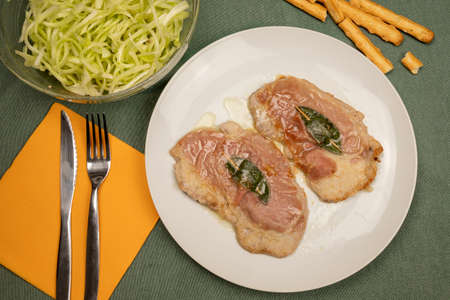 Saltimbocca alla romana (veal with raw ham and sage) on the plate. Flat lay. Typical second course of Roman cuisine.