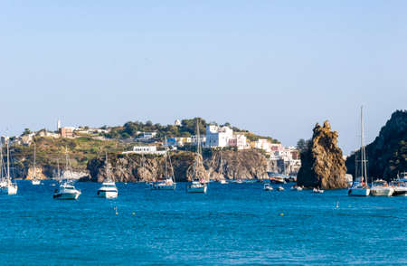 Beautiful view of the island of Ponza along the way from the port to the beach of Frontone with the boats, rocks and houses above the rocks.