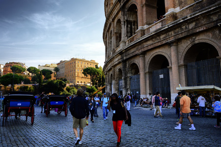 Rome. Tourists and carts near the walls of the Colosseum