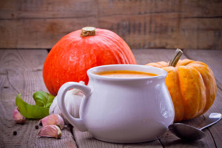 Pumpkin soup with pumpkins over wooden background photo