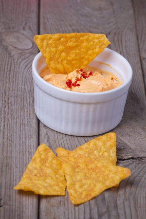 Nachos with dip over wooden background photo