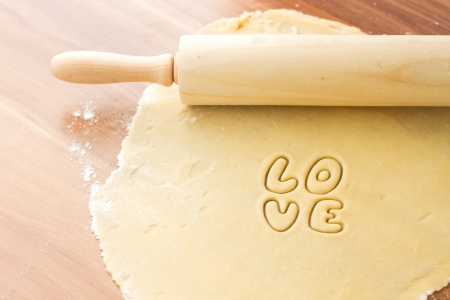 Dough with rolling, preparation for baking cookies, cut form love photo