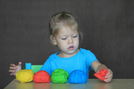 little girl playing with colorful dough